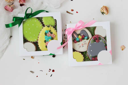 Easter colorful gingerbread in the shape of an egg with a rabbit drawn on them and flowers in a gift box. Close up. Archivio Fotografico