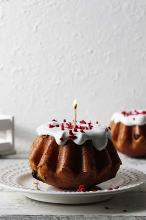 Rum baba poured with white icing on a plate on a table covered with a white tablecloth. Close up.