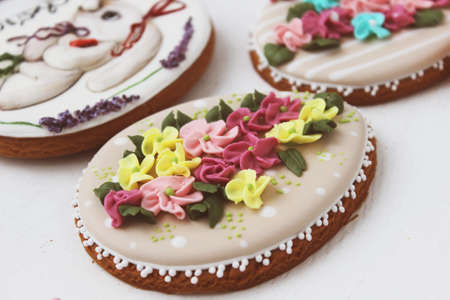 Easter colored gingerbread in the shape of an egg with a rabbit and flowers drawn on them. Close up.
