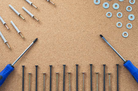 Repair. Self-tapping screws, washers, and screwdrivers on the desktop. The concept of a repair shop Close-up.