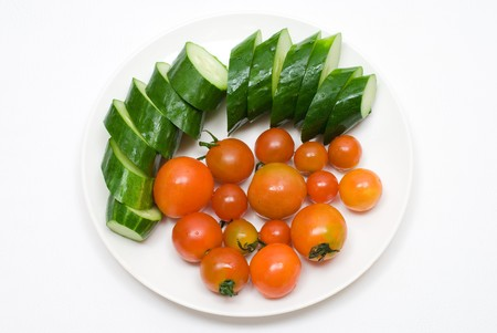 colord: Small tomato and cucumber on the plate