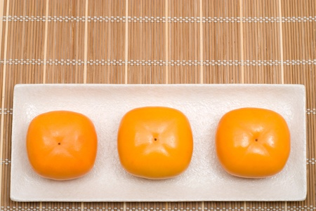 colord: Row of three persimmon on the plate