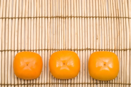 colord: Row of three persimmon on the Ditch reed mat Stock Photo
