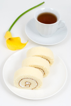 Swiss roll and tea with Yellow calla lily photo