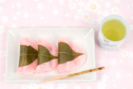 Japanese rice cake covered with sweetened bean jam wrapped in a preserved cherry leaf named Choumeiji-sakuramochi(East style sakuramochi) 스톡 콘텐츠