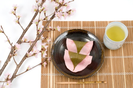 Japanese rice cake covered with sweetened bean jam wrapped in a preserved cherry leaf named Choumeiji-sakuramochi(East style sakuramochi) photo