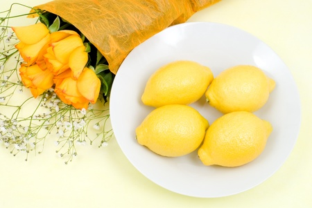 sourness: Lemon on a plate with rose bouquet Stock Photo
