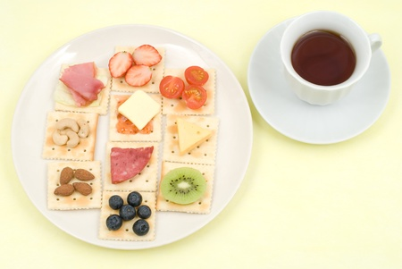 Various food topped Crackers and tea photo