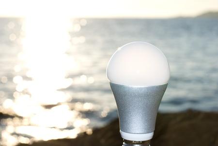 LED light bulb standing at the glitter seaside Stock Photo
