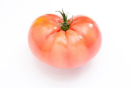 One heart shaped tomato isolated on white background photo