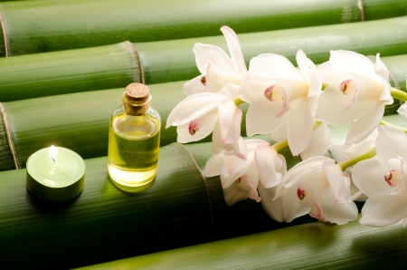 Essential oil and white orchid flowers on a tightly arranged large bamboo background photo