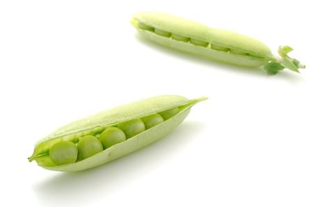 diagonally: Two pea pods were placed diagonally on a white background