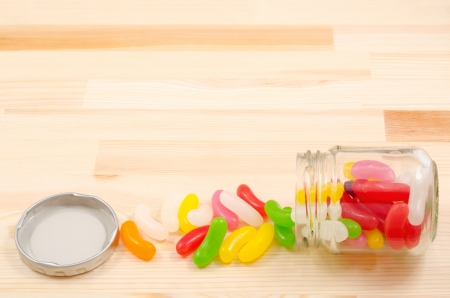 Colorful jelly beans spilled from clear glass jar on wooden board photo