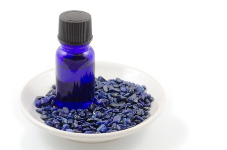 lapis: Essential oil and lapis lazuli gemstone on the plate