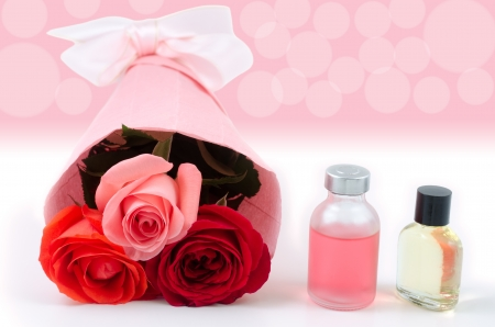 Rose bouquet and essential oil in front of pink blur Stock Photo - 16431944