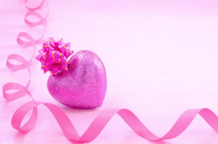 tilting: Heart shaped gift placed tilting and ribbon on a pale pink background Stock Photo