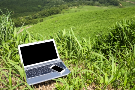 Notebook computer and smart phone on green highland