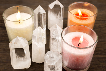 Quartz crystals aligned and lighted color candles photo