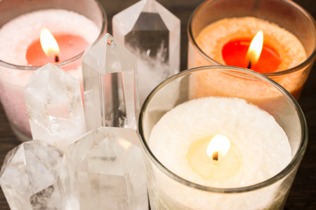 Close up of quartz crystals aligned and lighted color candles photo