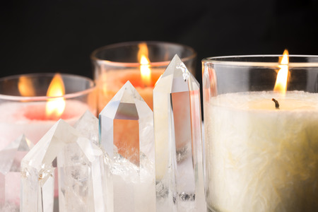 Close up of quartz crystals lined and lighted color candles when viewed from side photo