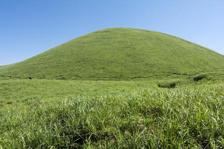 hemispherical: Green hemispherical hill in the grassy plain under blue sky