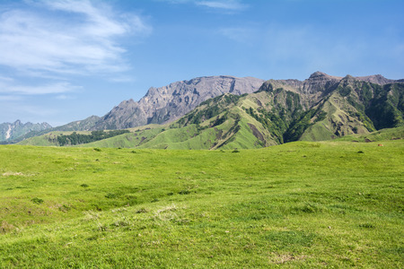 Undulating mountain peaks and grassy plain under blue sky Фото со стока