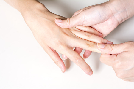 dorsal: Woman hand finger dorsal to receive a massage on pale gray background