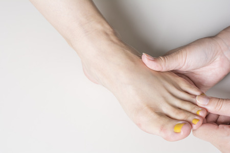 dorsal: Woman foot finger dorsal to receive a massage on pale gray background
