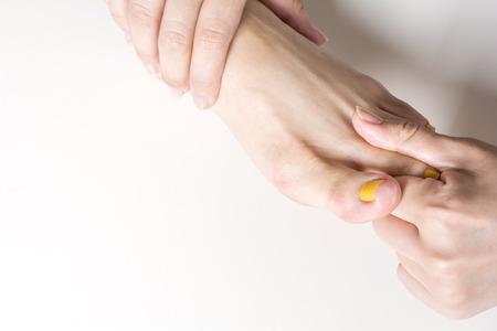 dorsal: Mujer dorsal del pie para recibir un masaje en el fondo gris p�lido