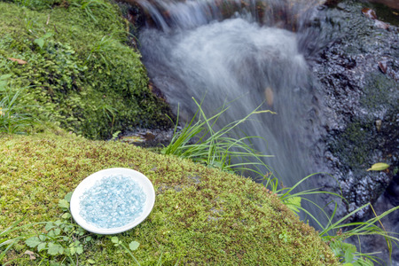 Aquamarine on plate with mossy stone at riverside photo