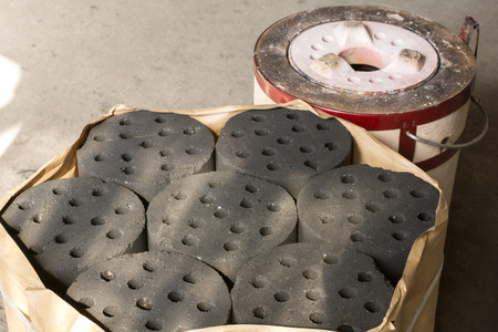 briquettes: Coal briquettes in front of soil briquette stove Stock Photo