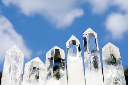obelisk: Six lined obelisk rock crystals under blue sky