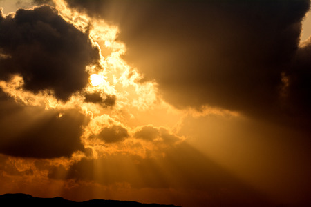 crepuscular: Crepuscular rays from floating clouds with sun at sunset