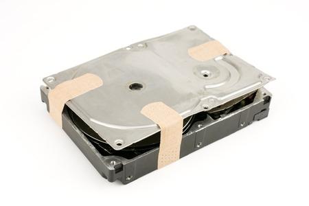 hard drive crash: Damaged hard disk drive put a adhesive plaster isolated on white background