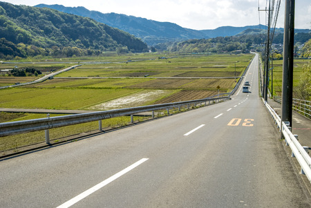 downhill: Downhill straight roadway and before planting rice fields Stock Photo