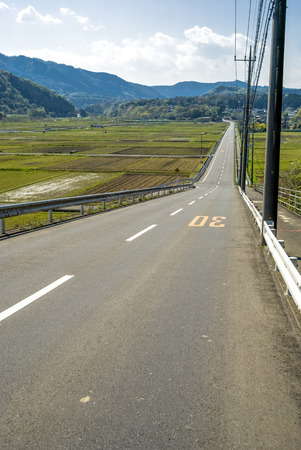 roadway: Downhill straight roadway and before planting rice fields in vertical composition Stock Photo