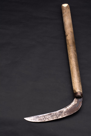 worn out: Worn out japanese sickle on dark background in vertical composition