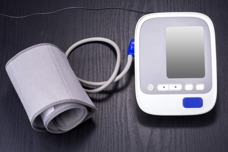 Electronic sphygmomanometer for household use on black table Stock Photo