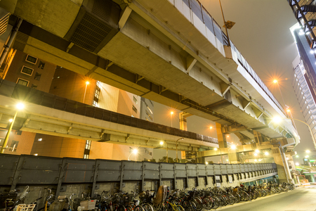 overlapped: Overlapped Tokyo metropolitan expressway and many parking bicycles at night Stock Photo
