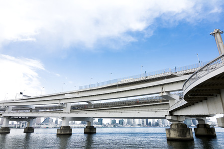 overlapped: Overlapped highway over the sea and dense buildings in Tokyo bay area under sky