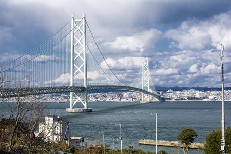 schlagbaum: Akashi Kaikyo-Brücke vor Kobe Stadtgebiet unter Himmel mit Wolken