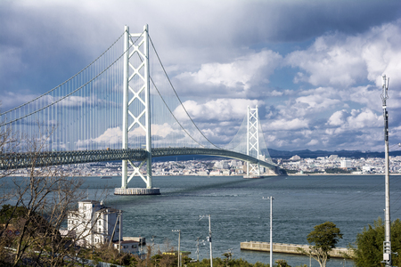 turnpike: Akashi kaikyo bridge in front of Kobe city area under sky with clouds