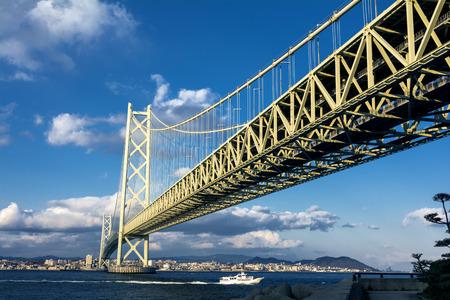 schlagbaum: Akashi Kaikyo-Br�cke und laufen Boot unter blauem Himmel