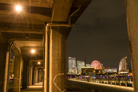 Under the overpass in front of amusement park and buildings in Yokohama at night Stock Photo