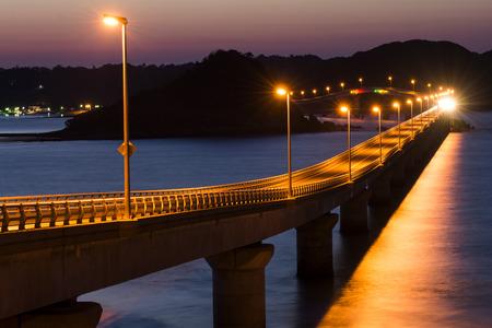 light up: Orange light up Tsunoshima Ohashi bridge with sea light reflections in Shimonoseki, Yamaguchi at twilight Stock Photo