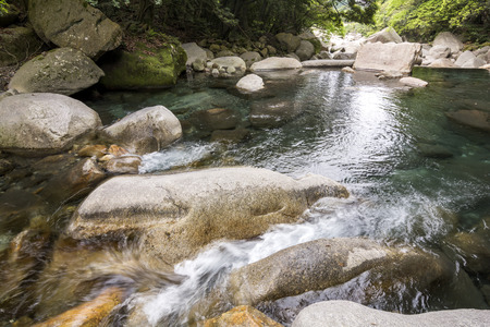 among: Brook spread out flowing through among a rocks Stock Photo