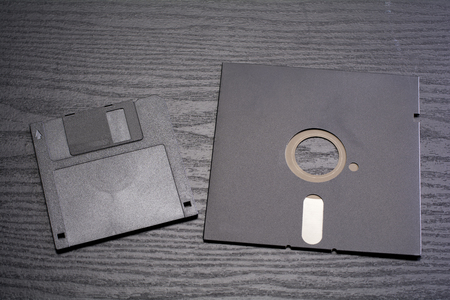 disks: 3.5-inch and 5.25 inch floppy disks on black desk Stock Photo