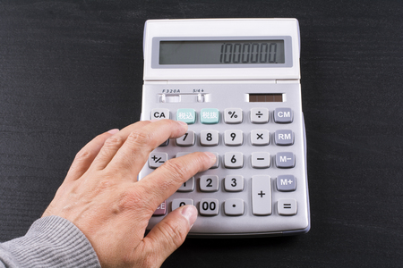 electrical materials: Finger doing calculation on calculator over black desk Stock Photo