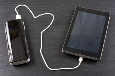rechargeable: Charging tablet from portable rechargeable battery on black desk