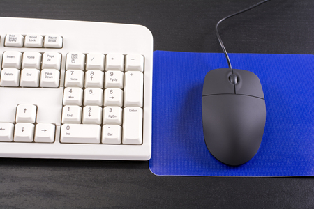 mouse pad: Computer keyboard and mouse with blue pad on black desk